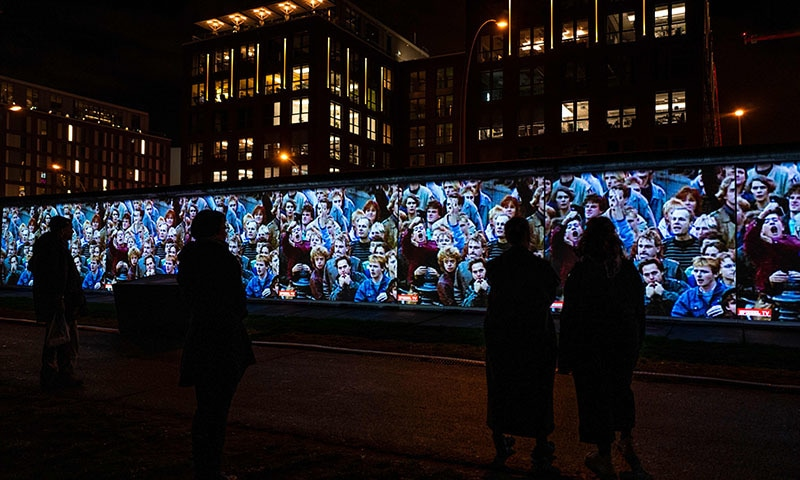 Footage showing mass demonstrations in the former east Germany is  projected on a stretch of the Berlin wall at the so-called East-side Gallery during the city-wide kick-off of the festival week to celebrate the 30th anniversary of the November 9,1989 fall of the Berlin Wall, in Berlin on November 4. — AFP
