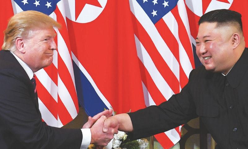 US President Donald Trump and North Korean leader Kim Jong Un all smiles as they shake hands in Hanoi in February last year. — AFP/File