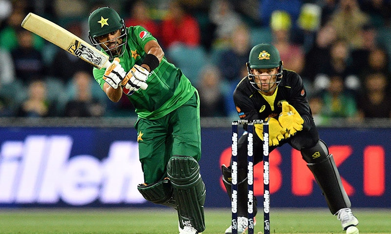 Babar Azam plays a shot as Australia's wicketkeeper Alex Carey (R) looks on during the second Twenty20 match between Australia and Pakistan at the Manuka Oval in Canberra on November 5. — AFP