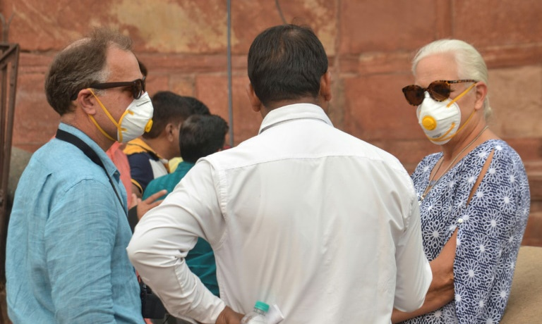 Foreign tourists wear face masks while visiting the famed Taj Mahal in Agra as smog levels soared. — AFP