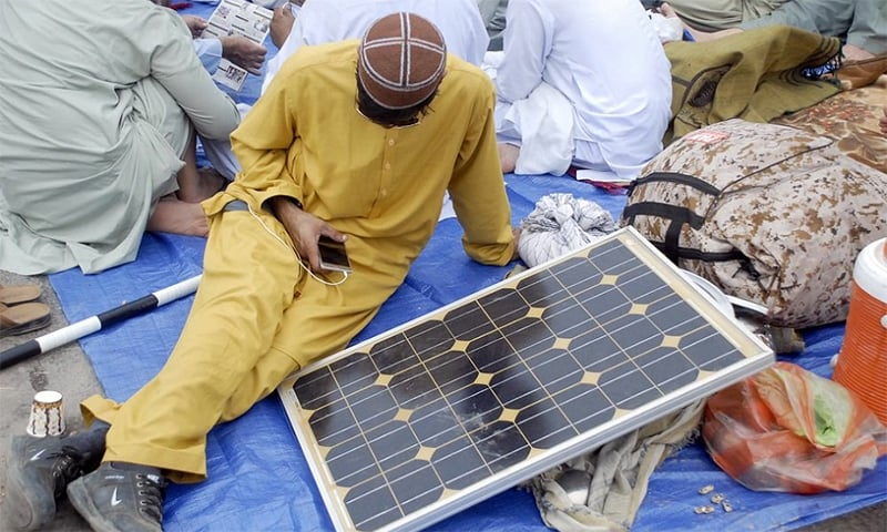 A protester charges his phone through a solar panel at the Azadi March sit-in in Islamabad. — Online