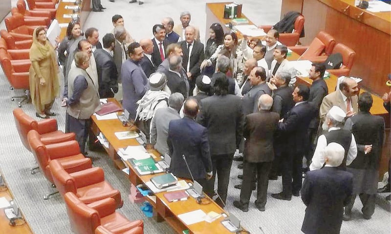ISLAMABAD: Senators belonging to the opposition parties assemble on Tuesday near the Senate chairman's podium in protest against the refusal to give a ruling binding the government to lay ordinances in the house.—INP