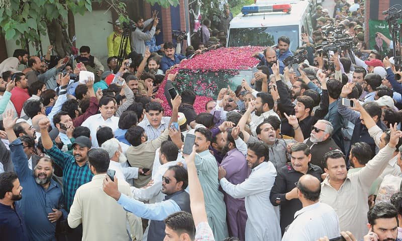 Supporters of the Pakistan Muslim League-N shower rose petals on vehicles carrying Nawaz Sharif and his daughter Maryam Nawaz from the hospital on Wednesday.—M. Arif / White Star