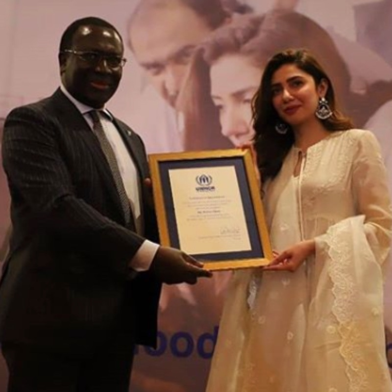 UNHCR's Assistant High Commissioner for Operations, Mr. George Okoth-Obbo presenting a certificate of appointment to Khan.