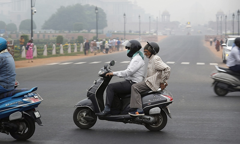 A man covers his face with a cloth and drives amidst smog in New Delhi, India on Thursday. — AP