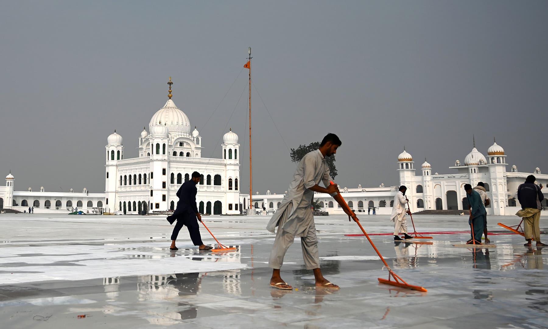 In this picture taken on November 6, workers clean the floor at the Shrine of Baba Guru Nanak Dev at the Gurdwara Darbar Sahib, ahead of its opening in Kartarpur. — AFP