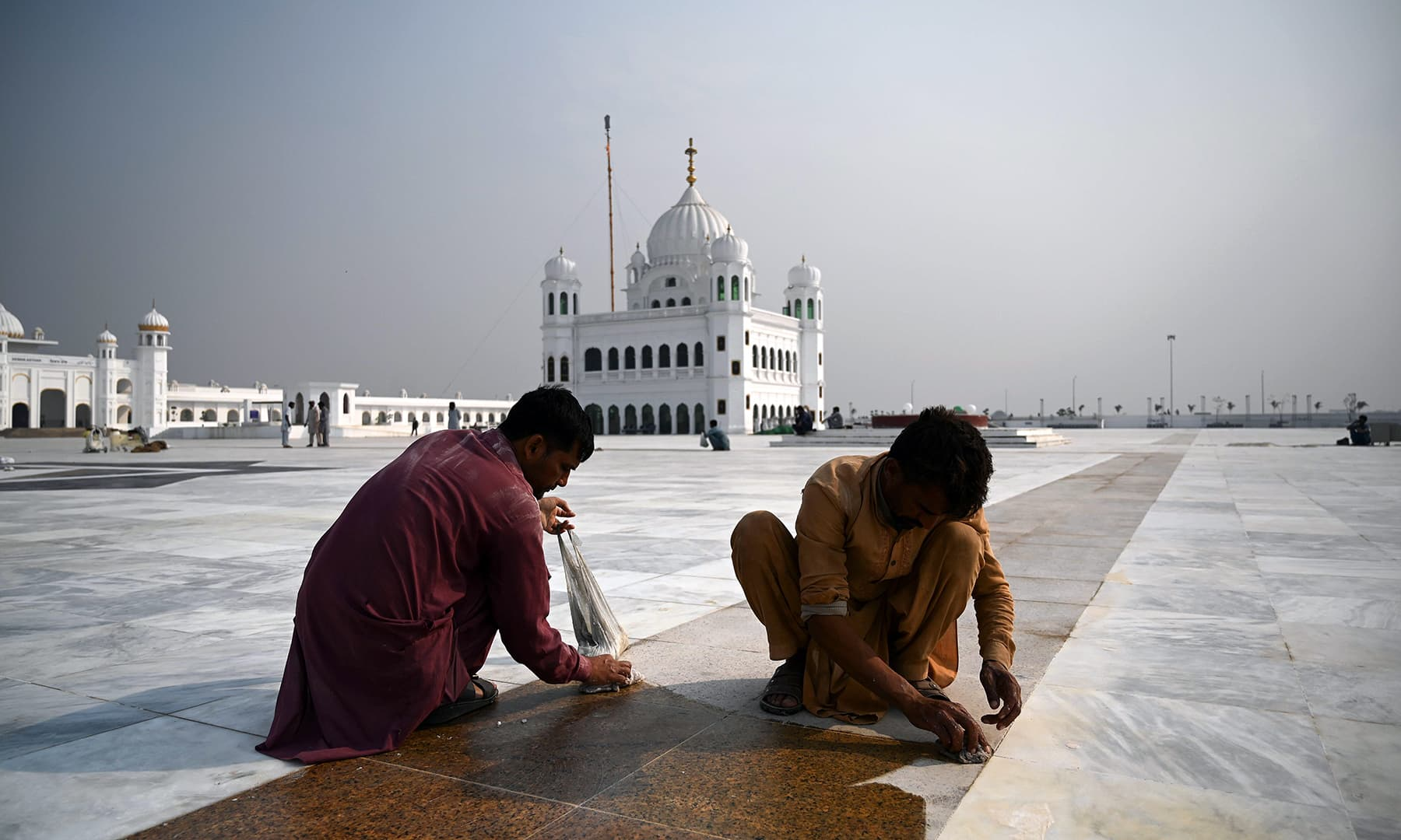 In this picture taken on November 6, workers shine a floor at the Shrine of Baba Guru Nanak Dev at the Gurdwara Darbar Sahib, ahead of its opening in Kartarpur. — AFP