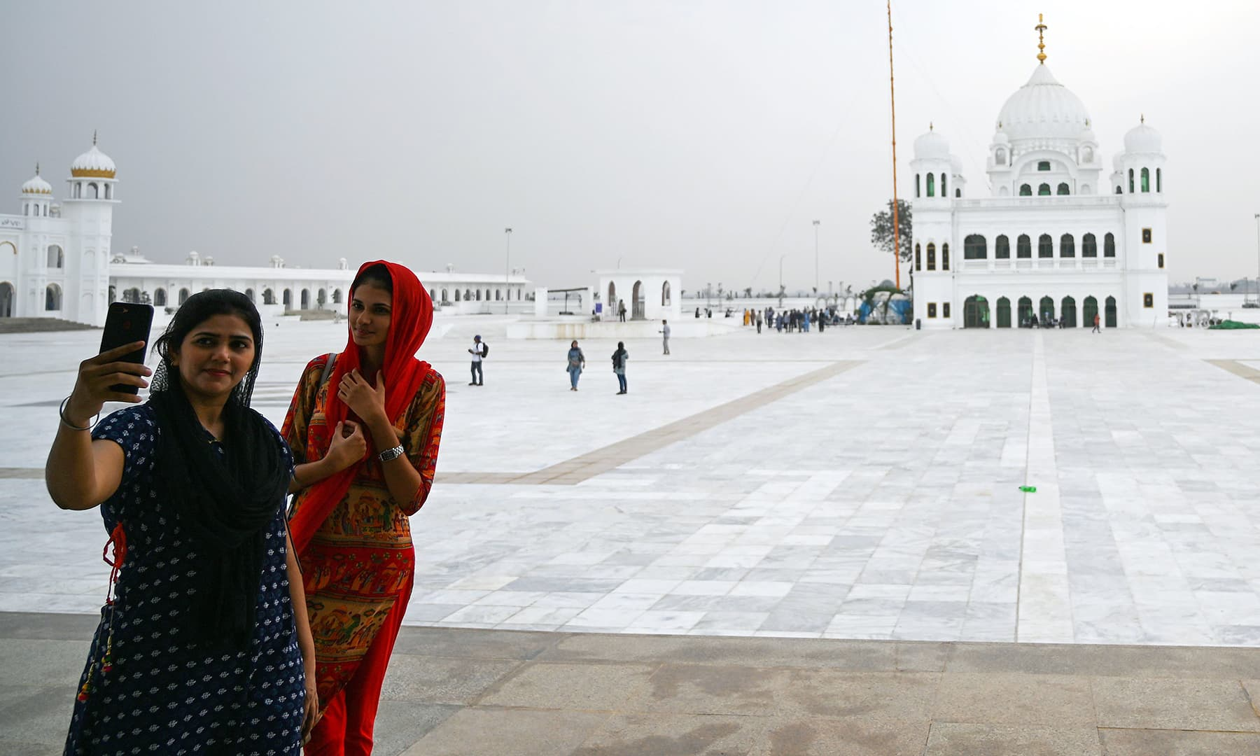 In this picture taken on November 6, Sikh pilgrims take selfies in front of the Shrine of Baba Guru Nanak Dev at the Gurdwara Darbar Sahib ahead of its opening, in Kartarpur. — AFP
