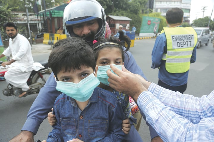 LAHORE: An environment ministry official provides masks to children on Thursday. Dangerously poor air quality forced the provincial government to close all schools in the city for the day. Punjab Chief Minister Usman Buzdar said the sudden increase in smog on Wednesday was the result of burning crops in India, along the border with Pakistan, accompanied by a change in wind direction.—AP