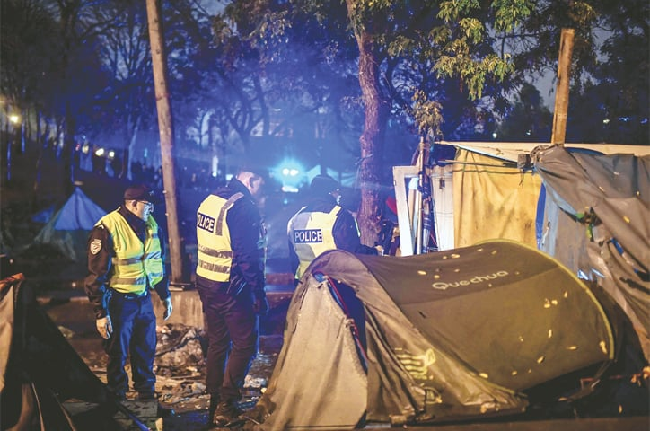 PARIS: Police evacuating migrants from their camps on Thursday.—AFP