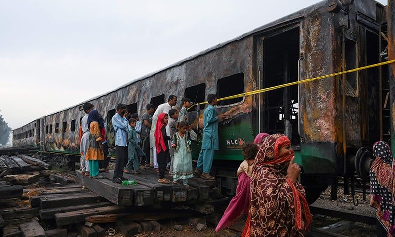 People looks at the burnt-out train carriages a day after a passenger train caught on fire in Rahim Yar Khan on November 1, 2019.  — AFP/File