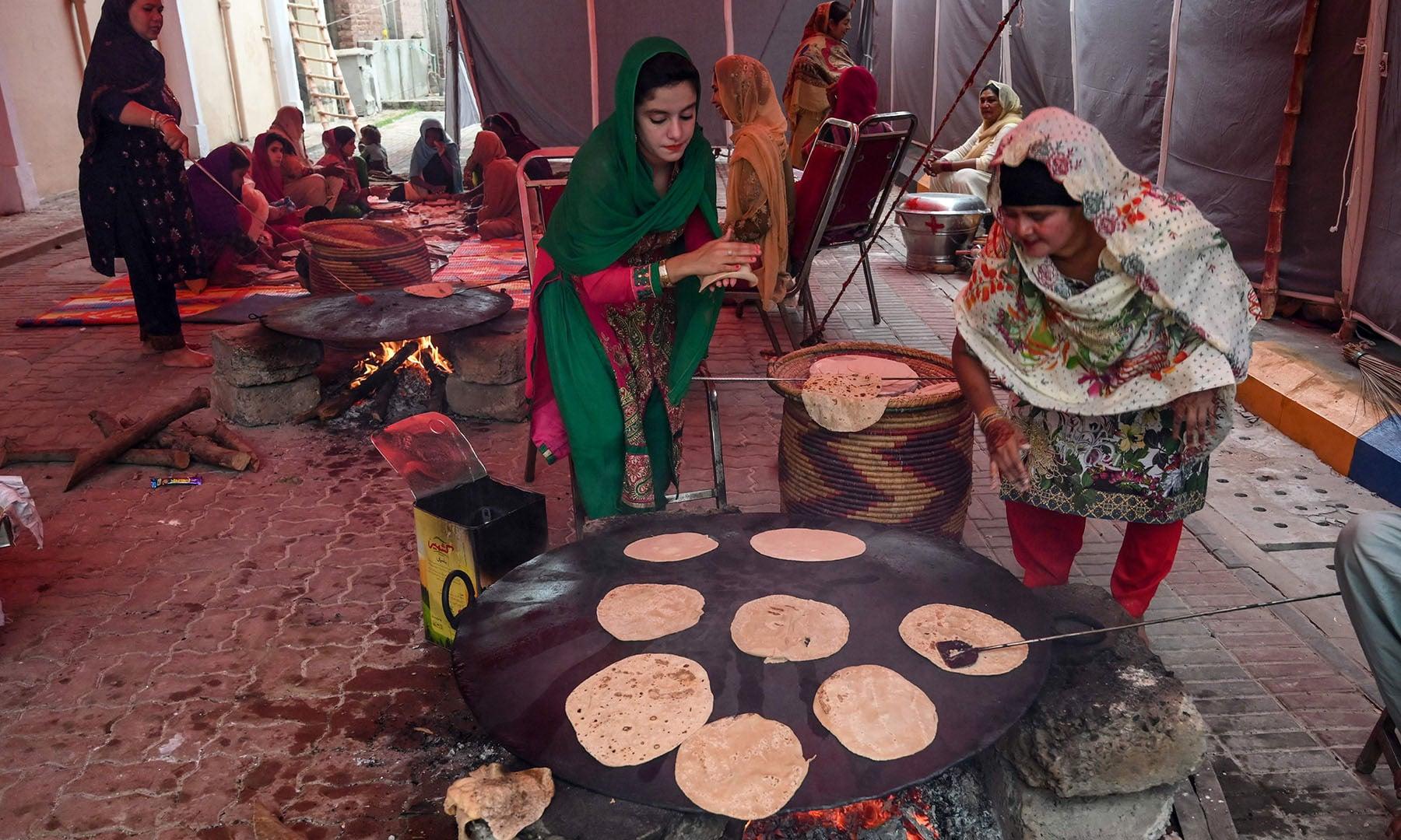 Sikh pilgrims prepare bread for devotees at a shrine in Nankana Sahib, some 75 km west of Lahore, on November 7. — AFP