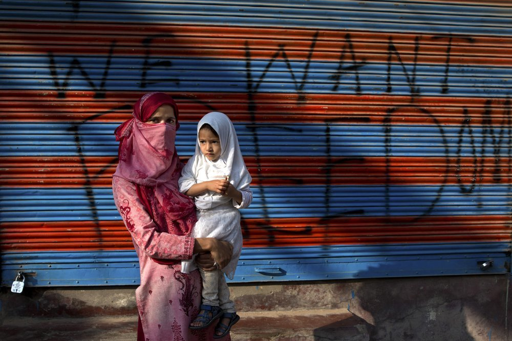 A Kashmiri woman protestor Jawahira Banoo, carries her 3-year-old daughter Rutba and stands for a photograph outside a closed shop with a spray-painted graffiti after a protest on the outskirts of Srinagar. Banoo says she does not miss an opportunity to come out to the streets to protest. ─ AP