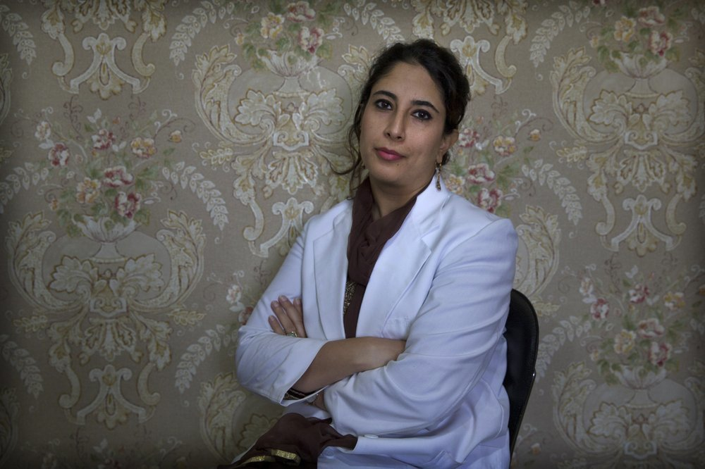 A Kashmiri doctor Sabahat Rasool sits for a photograph inside her clinic in Srinagar. Rasool says she's seen the lockdown forever alter lives. ─ AP