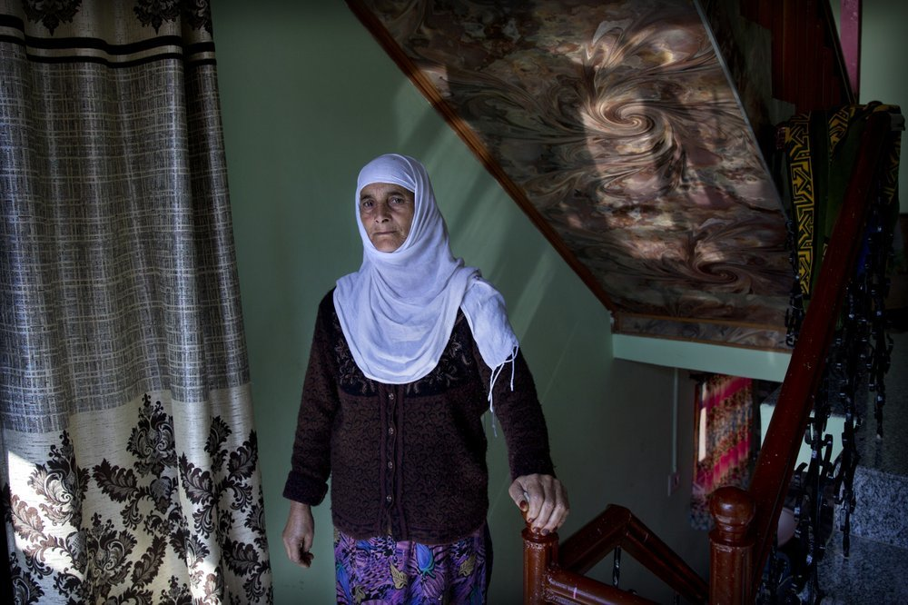 "A Kashmiri woman Biba Malla stands for a photograph inside her house on the outskirts of Srinagar. Malla's cousin died on Aug 31, but she was informed about it almost a week later. ""I missed the funeral and the Fateha Khawani. Our menfolk still haven't visited fearing detention by police on the way to our relative's home,"" she said. ─ AP"