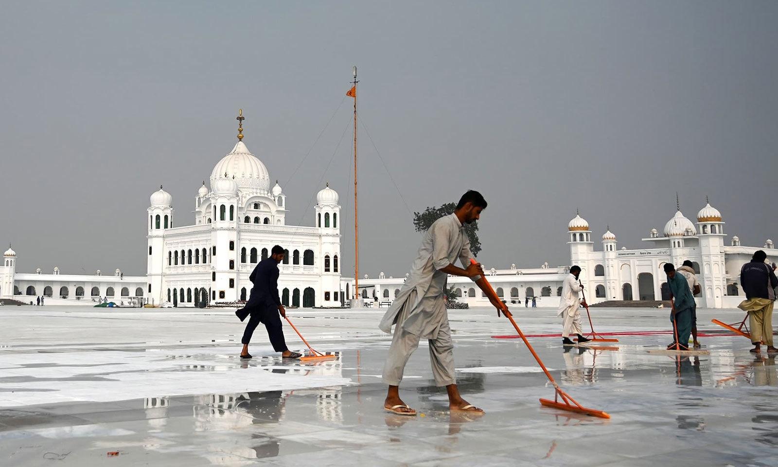 مزدور گوردوارہ دربار صاحب کا فرش چمکانے میں مصروف ہیں — فوٹو: اے ایف پی