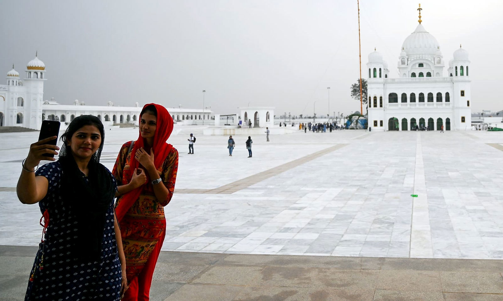 بابا گرونانک کے مزار کے سامنے سکھ زائرین سیلفیاں لے رہے ہیں — فوٹو: اے ایف پی