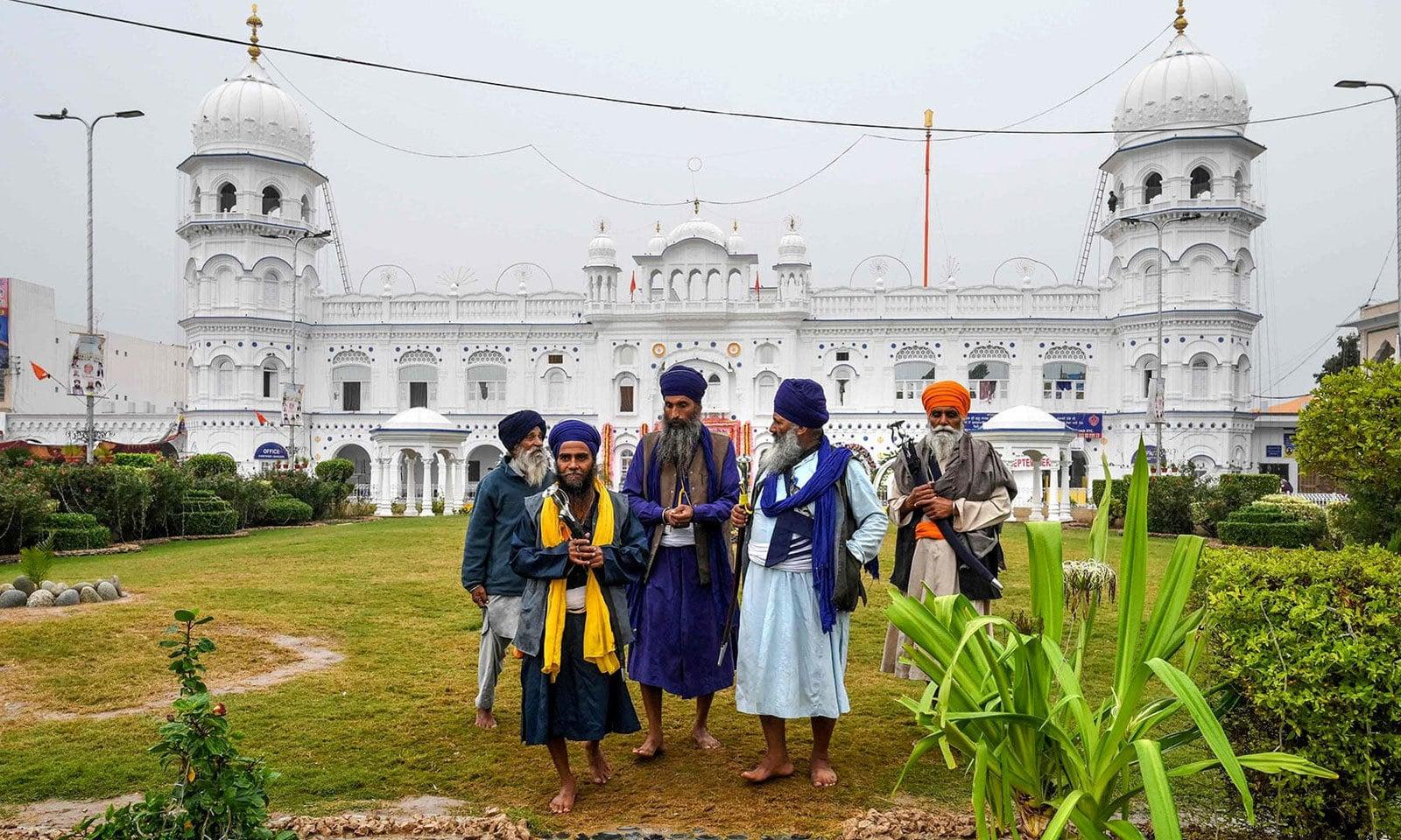 سکھ زائرین مزار کی زیارت کے بعد باہر آرہے ہیں — فوٹو: اے ایف پی