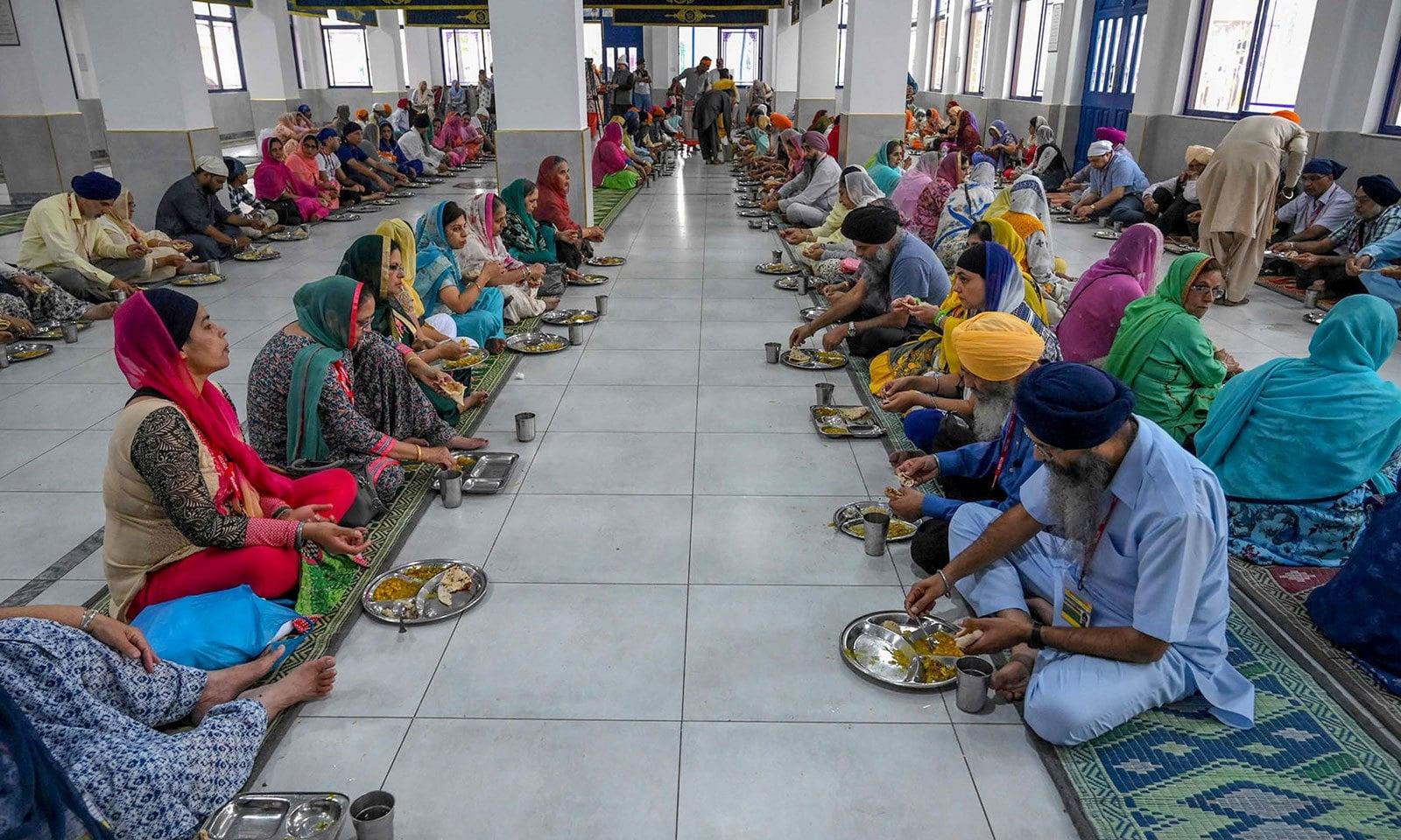 مزار میں سکھ زائرین طعام کر رہے ہیں — فوٹو: اے ایف پی