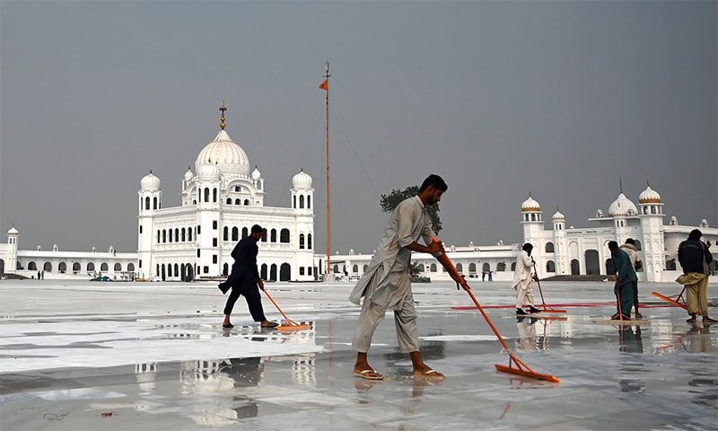 In this picture taken on November 6, workers clean the floor at the Shrine of Baba Guru Nanak Dev at the Gurdwara Darbar Sahib, ahead of its opening in Kartarpur. — AFP