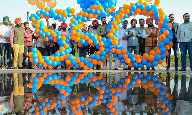 People hold balloons arranged in the shape of number 550, ahead of the 550th birth anniversary of Guru Nanak Dev, in Amritsar on November 8. — AFP