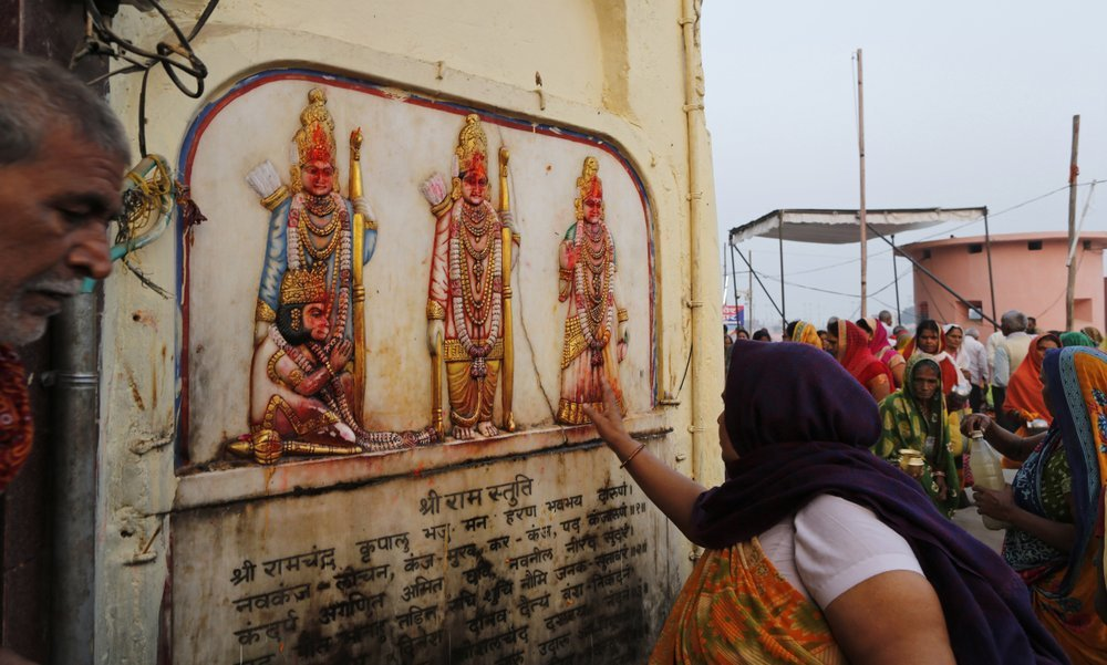 A Hindu pilgrim touches in obeisance an image of Hindu deities Rama, Sita and Lakshman in Ayodhya, India on Saturday. ─ AP