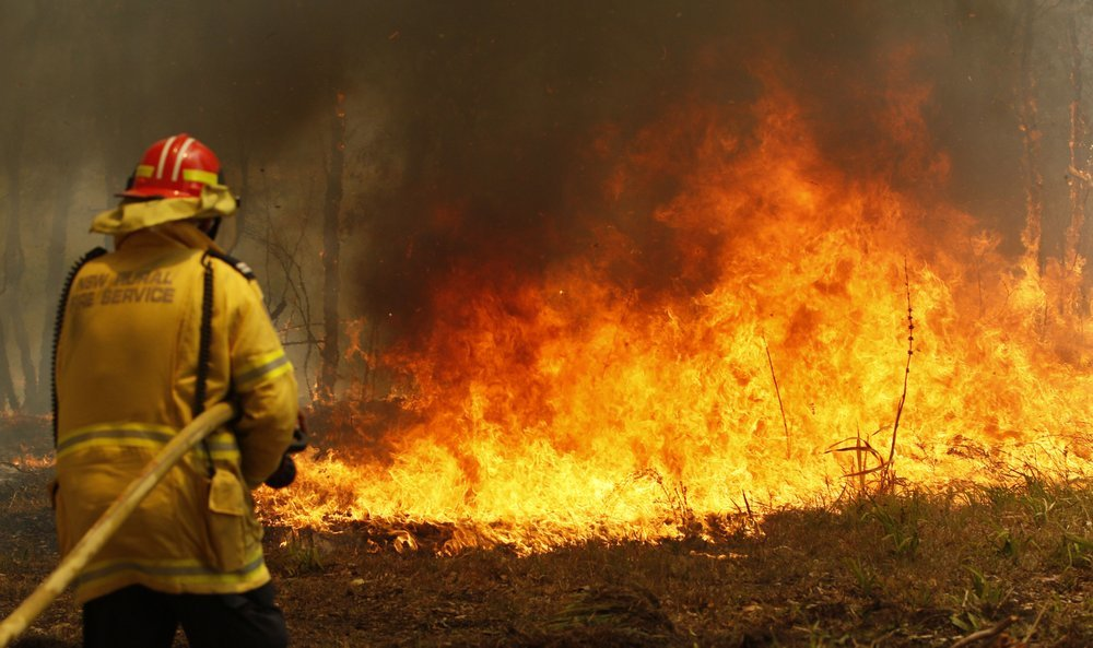 Firefighters work to contain a bushfire along Old Bar road in Australia on Saturday. — AP