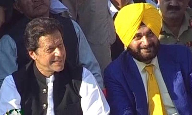 PM Imran Khan sits on the floor with former Indian cricketer-turned-politician Navjot Singh Sidhu. — DawnNewsTV