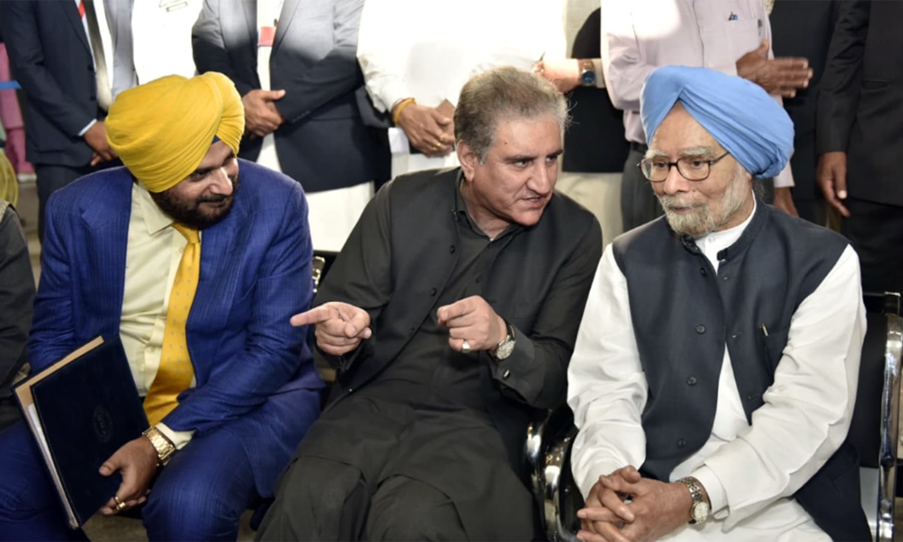 Shah Mahmood Qureshi speaking with former Indian premier Manmohan Singh and cricketer-turned-politician Navjot Singh Sidhu. — Foreign Office