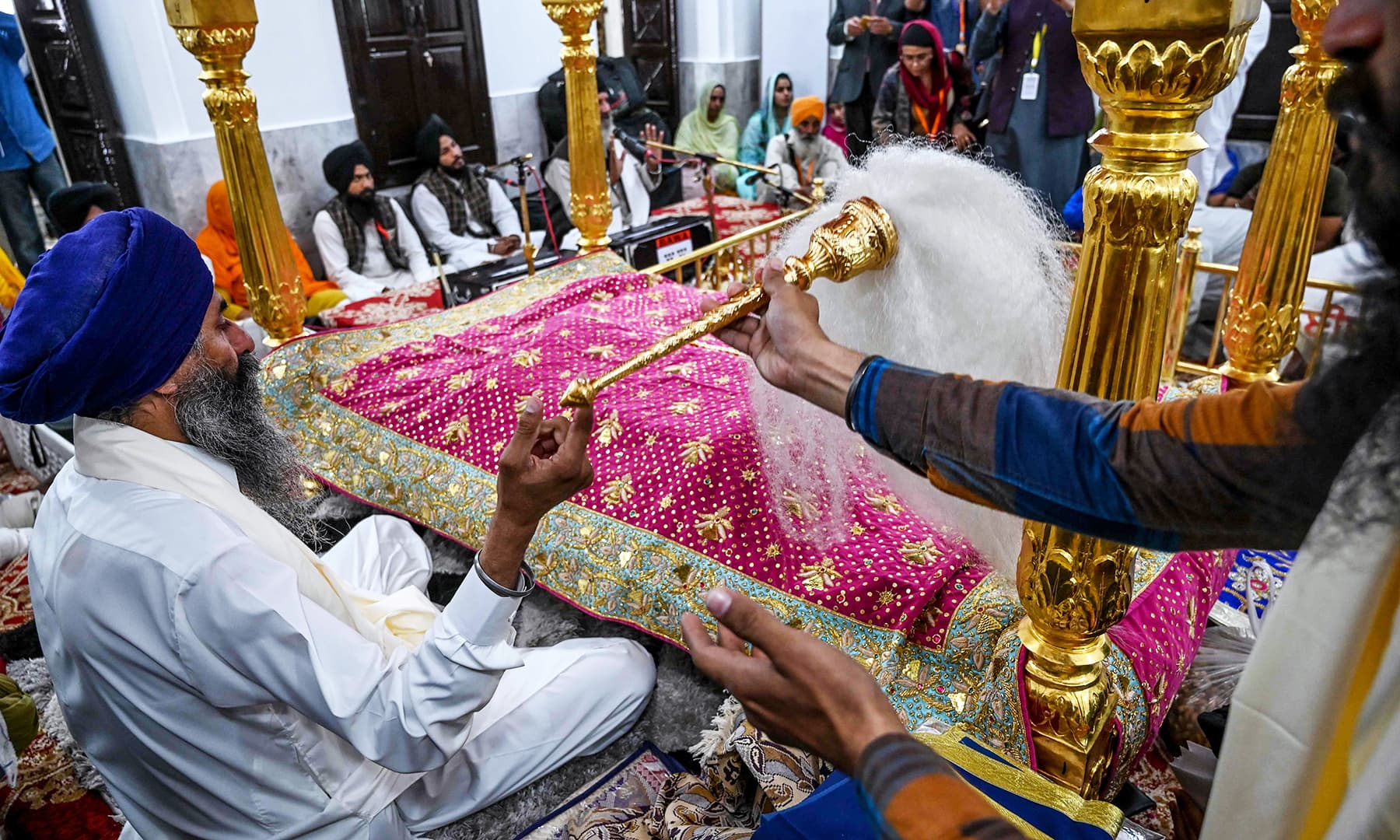 Sikh pilgrims take part in a religious ritual at the Shrine of Baba Guru Nanak Dev at Gurdwara Darbar Sahib in Kartarpur on Saturday. — AFP