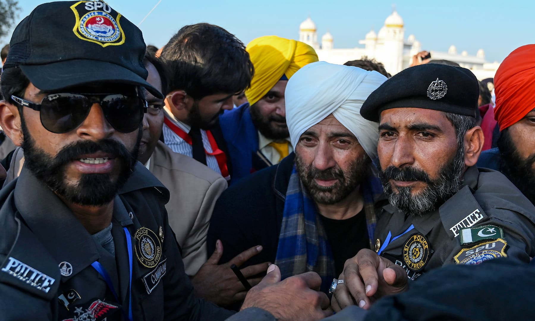 Security personnel escort Indian politician and former cricketer Navjot Singh Sidhu (L) and Indian Bollywood actor Sunny Deol as they visit the Shrine of Baba Guru Nanak Dev at Gurdwara Darbar Sahib in Kartarpur on Saturday. — AFP