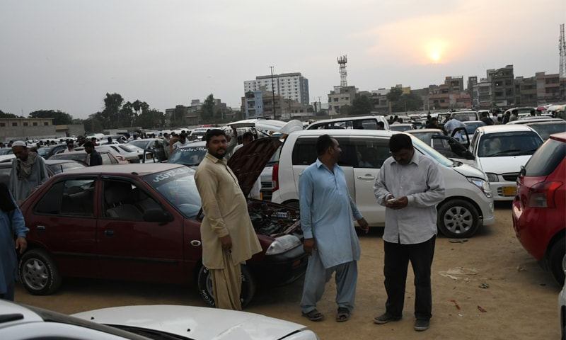 People survey cars in a bazaar for used car sales in Karachi