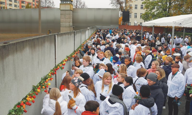 People place roses into a gap at the Wall memorial during a ceremony marking the 30th anniversary of the fall of the Berlin Wall on Saturday.—Reuters