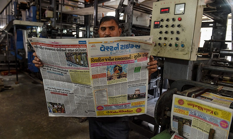 A machine operator reads the newspaper as the front page of the Gujarati-language 'Western Times' features the news of Indian Supreme Court's verdict on disputed religious site in Ayodhya, on the outskirts of Shilaj village, some 20 kms from Ahmedabad on November 9. — AFP
