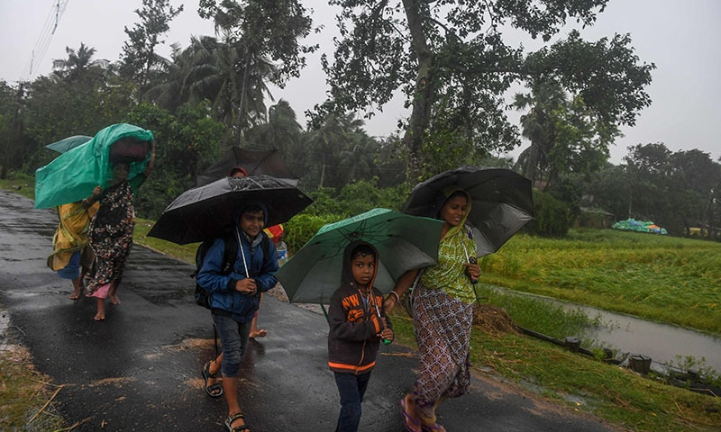 Villagers holding umbrellas carry their belongings on their way to enter a relief centre as Cyclone Bulbul is approaching, in Bakkhali near Namkhana in Indian state of West Bengal on November 9. — AFP