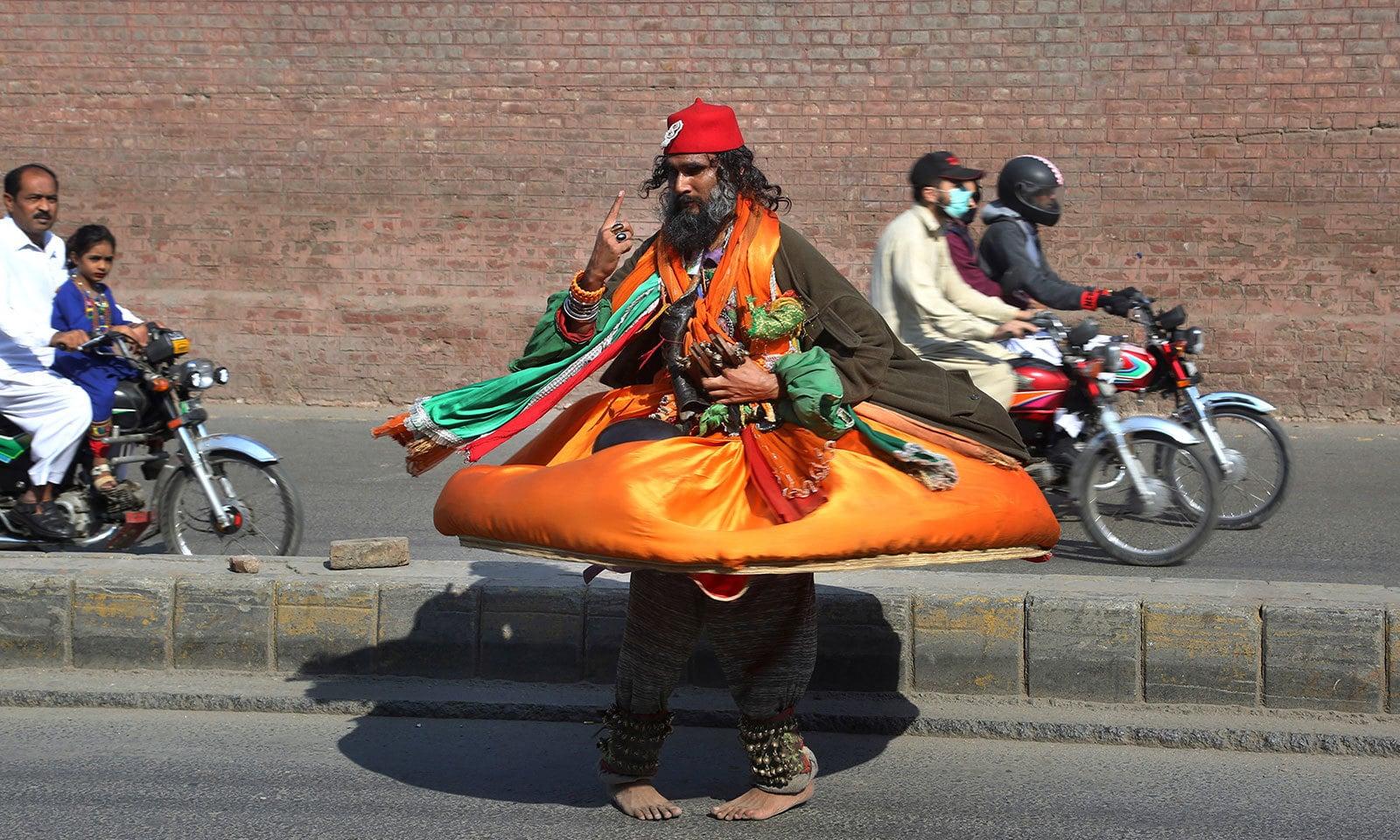 لاہور کی ایک سڑک پر درویش جشن مناتے ہوئے—فوٹو:اے پی