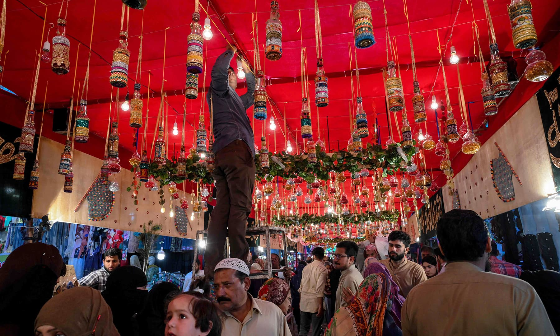 A man decorates a street to mark Eid-i-Miladun Nabi, in Lahore on Saturday. — AFP