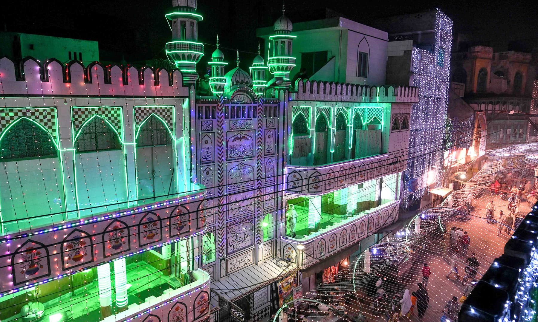 People walk in a street decorated to mark Eid-i-Miladun Nabi in Lahore on Saturday. — AFP