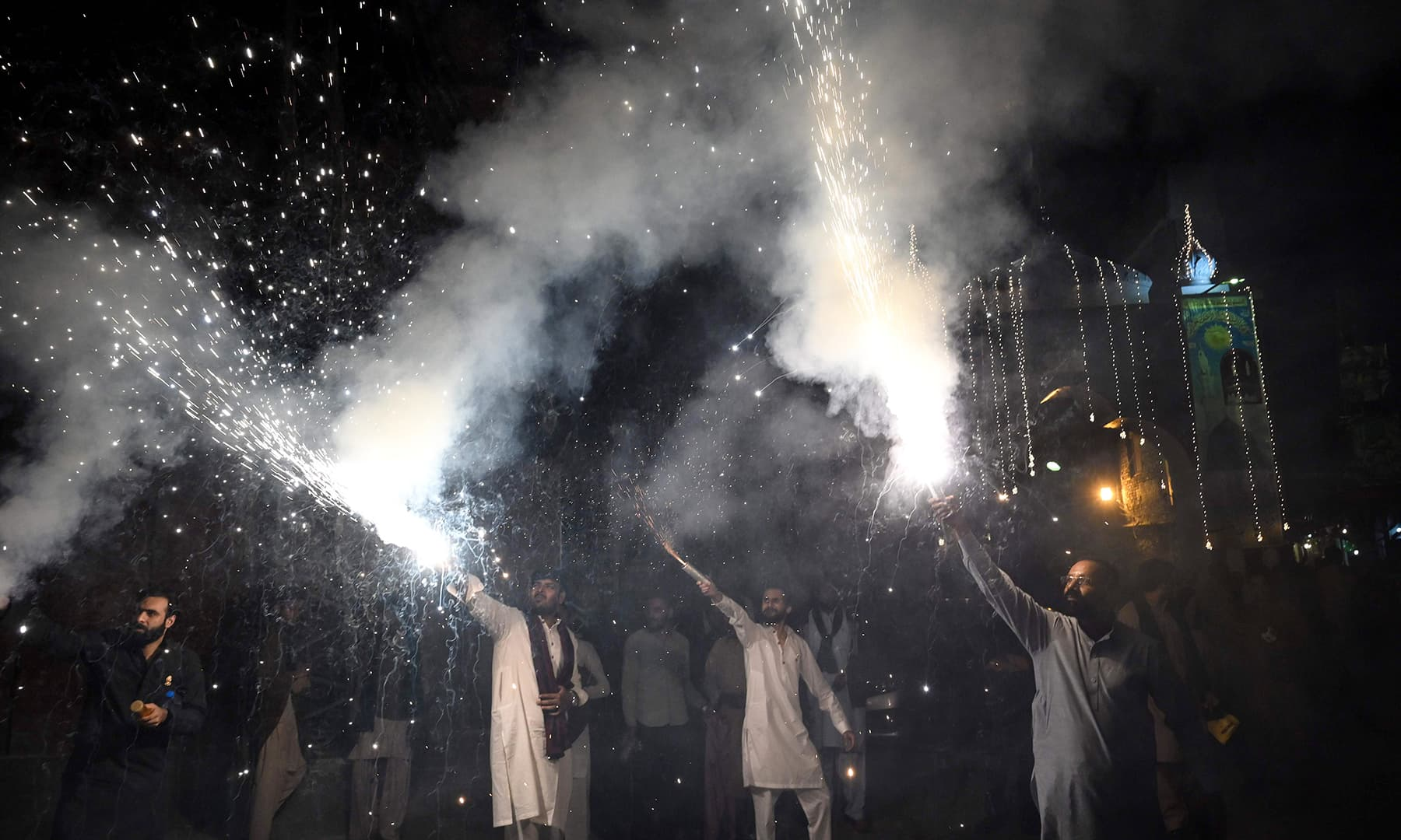 People celebrate with fireworks on the eve of Eid-i-Miladun Nabi in Lahore on Saturday. — AFP
