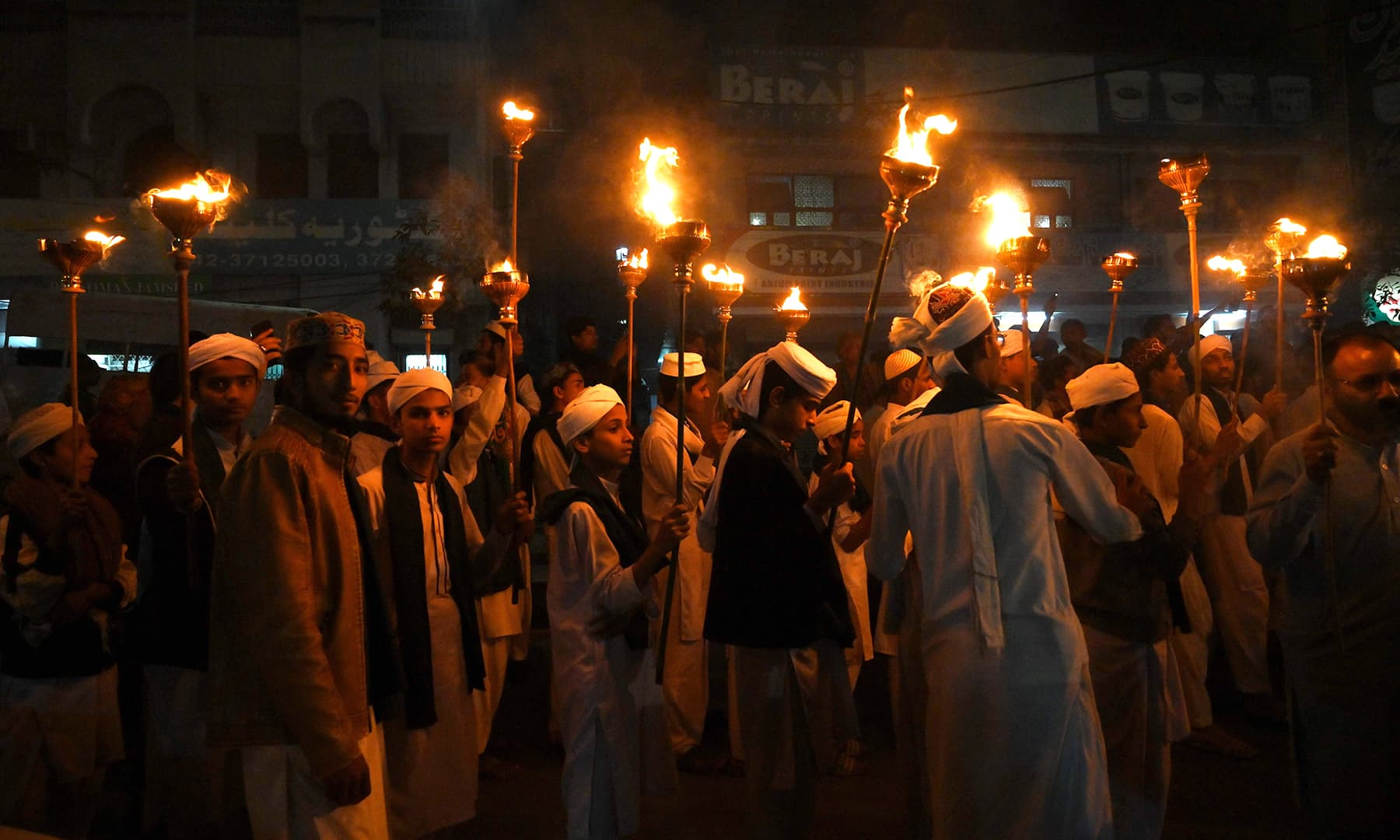 Children hold torches in a rally to mark 12 Rabi-ul-Awwal, in Lahore on Saturday. — AFP