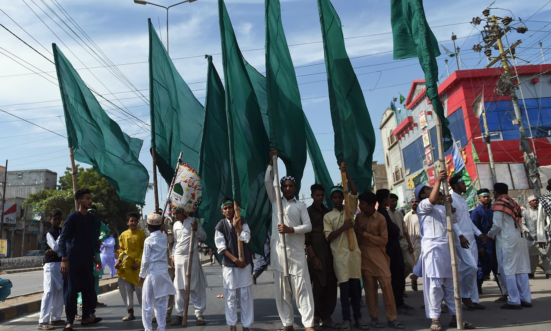 Devotees carry flags in a procession to mark 12 Rabi-ul-Awwal in Karachi on Sunday. — AFP