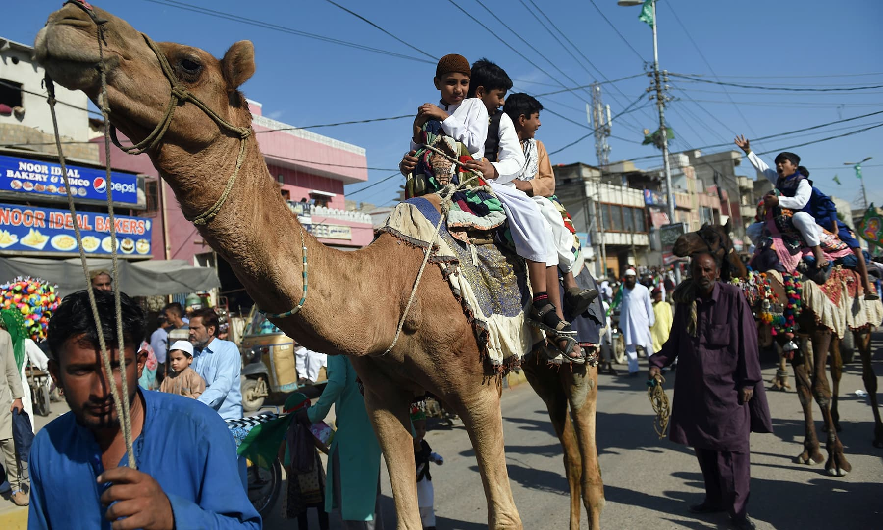 Children sit on camels as they participate in a procession to celebrate the birth of the Holy Prophet (PBUH), in Karachi on Sunday. — AFP
