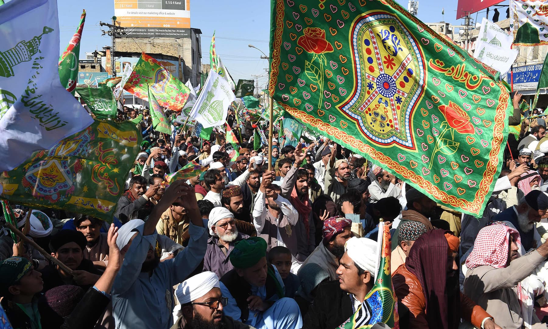Participants carry flags as they march in a procession o celebrate the birth of the Holy Prophet (PBUH), in Karachi on Sunday. — AFP