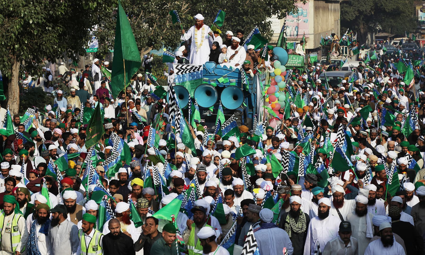 Men wave flags as they attend a procession to mark Eid-e-Milad-ul-Nabi, in Lahore, on Sunday. — Reuters