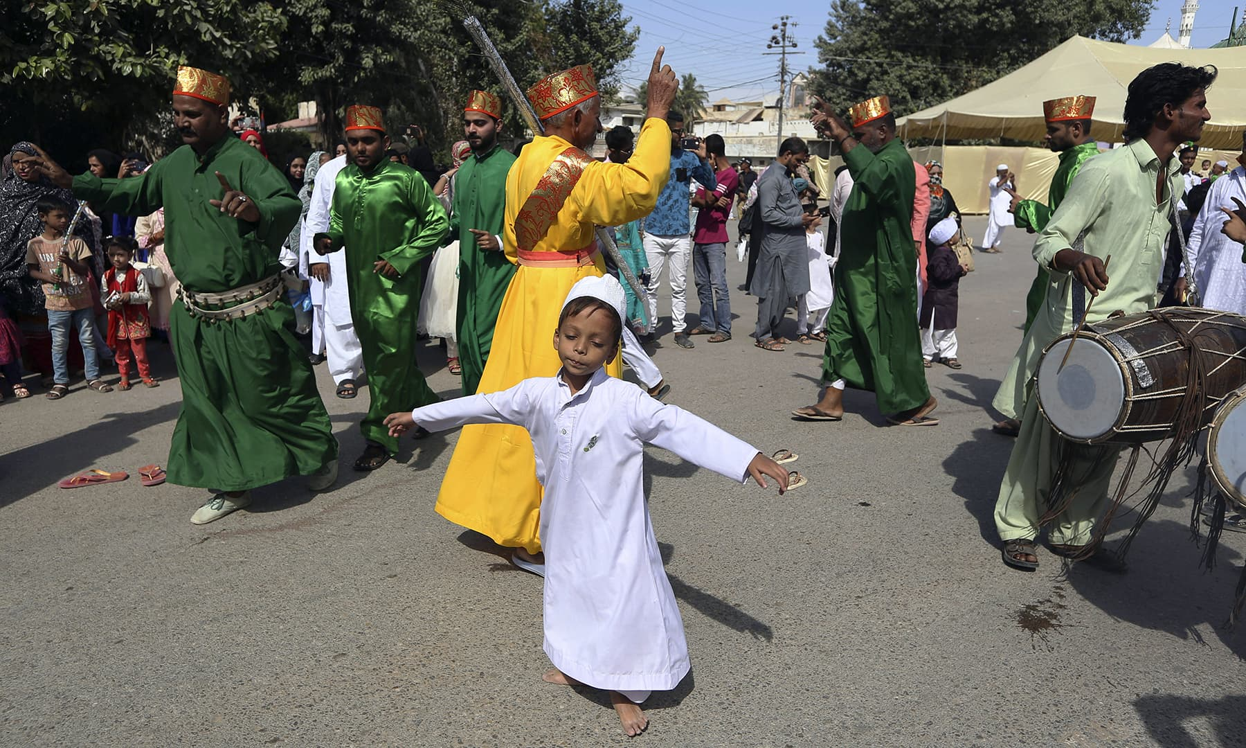 A boy performs a traditional dance with others during a rally to celebrate Eid-i-Miladun Nabi in Karachi, on Sunday. — AP