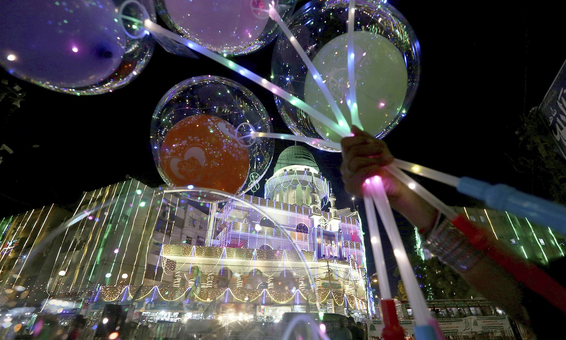 A street vendor holds lighted balloons next to a mosque, decorated with lights for Eid-i-Miladun Nabi, in Karachi, on Saturday. — AP