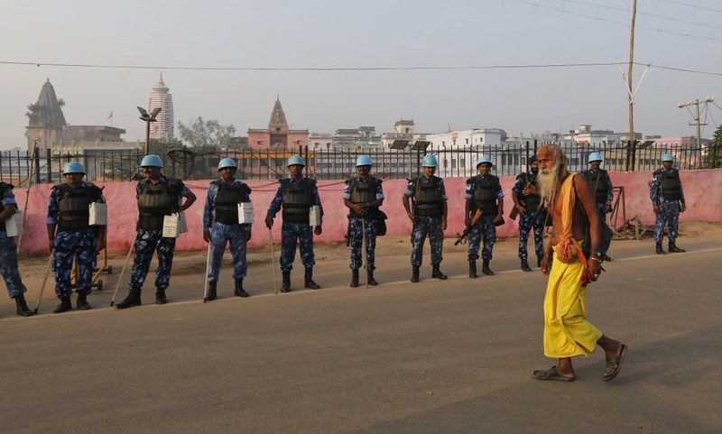 A Sadhu, Hindu holy man, walks past security officers standing guard in Ayodhya on Saturday. — AP/File