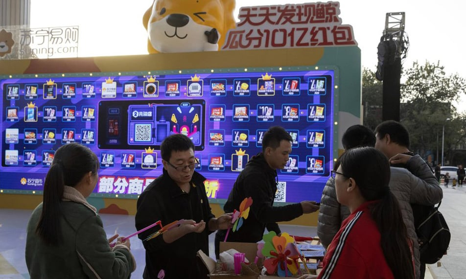 Promoters hand out free gifts on Sunday as part of a game to promote Nov 11 Singles day in Beijing. — AP