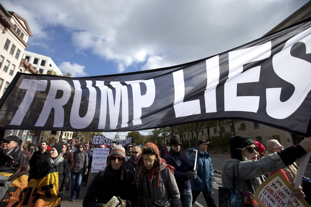 Demonstrators march on Pennsylvania Avenue in Washington on Nov 8 protesting against climate policies and to impeach President Donald Trump. ─ AP