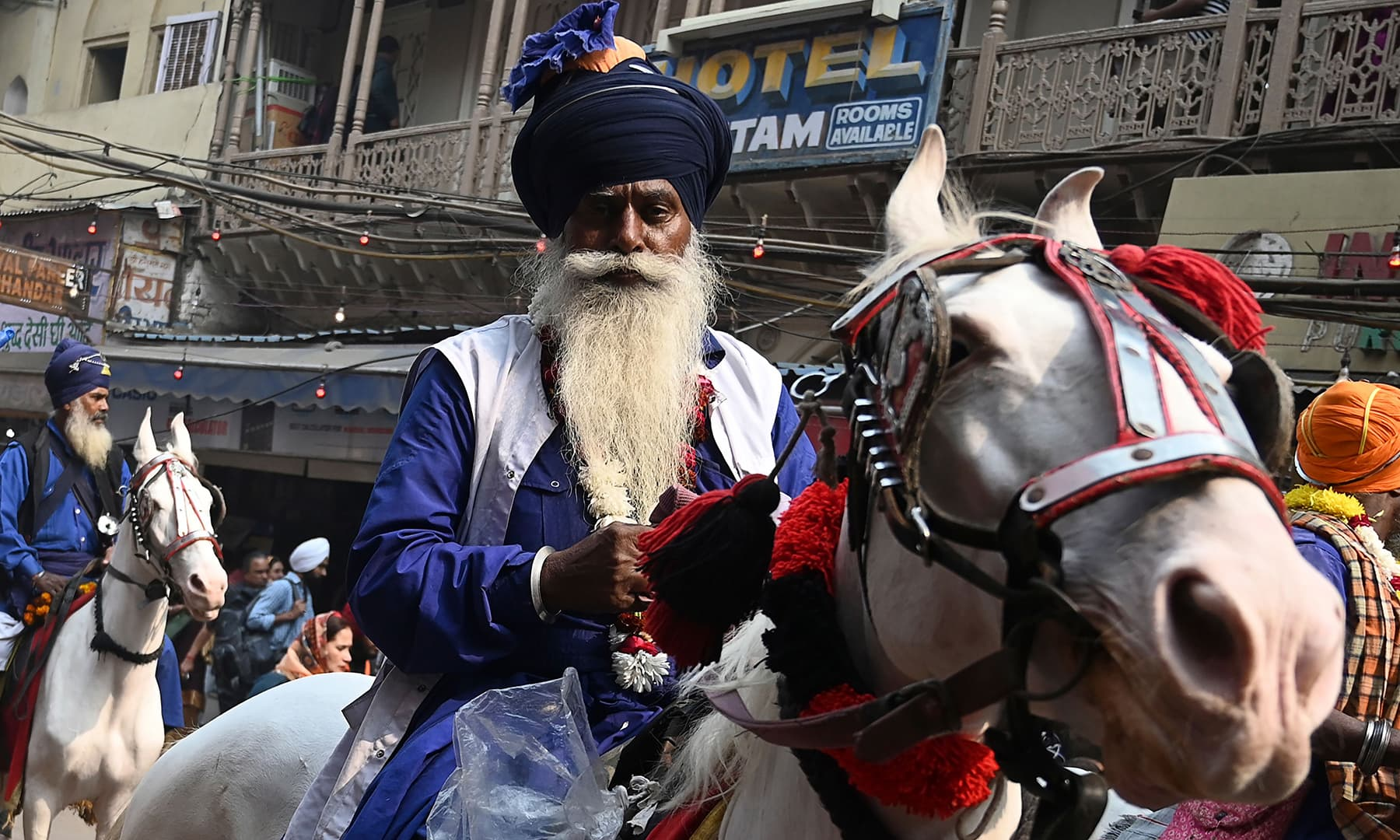 "A Nihang, Sikh man who belongs to the armed Sikh order, rides his horse as he participates in ""Nagar Kirtan"" (religious procession) on the eve of the 550th birth anniversary of Sikhism founder Guru Nanak Dev in New Delhi on November 11. — AFP"